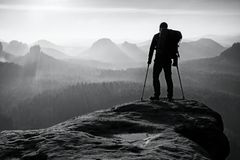 Tourist with leg in immobilizer. Hiker silhouette with medicine crutch on mountain. Peak. Deep misty valley bellow silhouette of man with hand in air. Spring Royalty Free Stock Images