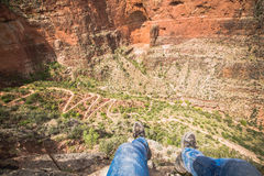 Tourist legs in wild valley of famous Grand canyon in summer day Stock Images