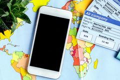 Tourist lifestyle with mobile and tickets map background top vie. Tourist lifestyle with mobile phone and flight tickets on map background top view Royalty Free Stock Image