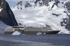 Tourist liner sailing among icebergs in Antarctica on a backgrou Stock Photos