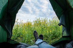 A tourist living in a tent with a view of canola field and a cloudy sky, stock image