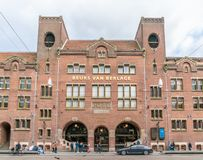 Tourist and locals passing the old trading building Beurs van Berlage on the Damrak. Named after the architect who build it. Amsterdam May 18 2018 - Tourist and stock photography