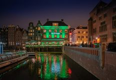 Tourist and locals passing an old trading building now used as the Grasshopper coffeeshop at night. Amsterdam May 18 2018 - tourist and locals passing an old royalty free stock photos