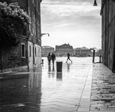 Tourist and locals people walking by the venetian street after the heavy rain in Venice, Italy. Venice - Italy, March 26, 2016: Tourist and locals people walking stock photo