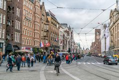 Tourist and locals walking on the Damrak. The street from the Central train station to the Dam square. Amsterdam May 18 2018 - Tourist and locals walking on the stock photography