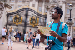 Tourist in london. Indian tourist outside buckingham palace holding a map and his camera Royalty Free Stock Image