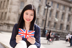Tourist in London. Japanese tourist reading a postcard in the street Royalty Free Stock Images