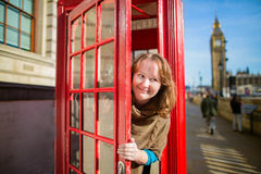 Tourist in London looking out of the phonebox Royalty Free Stock Photo