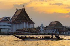 Tourist long trail boat is running through the temple. During sunset in Bangkok stock photography