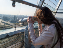 Tourist look observant binoculars telescope on panoramic view. Lifestyle concept trip, traveler with backpack on background city Royalty Free Stock Photos
