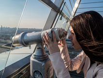 Tourist look observant binoculars telescope on panoramic view. Lifestyle concept trip, traveler with backpack on background city Royalty Free Stock Photo
