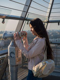 Tourist look observant binoculars telescope on panoramic view. Lifestyle concept trip, traveler with backpack on background city Stock Photography