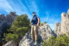 Tourist looking around with camera in hand, standing on the rock, blue sky and clouds, travel concept Stock Photography