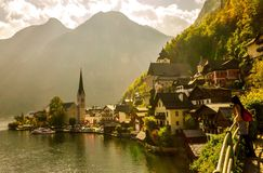 Tourist looking at beautiful view. Of village Hallstatt, lake and mountain in Austria, Europe, spring season Royalty Free Stock Image