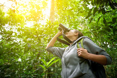 Tourist looking through binoculars considers wild birds in the j Royalty Free Stock Photography