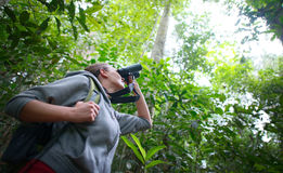 Tourist looking through binoculars exploring the wild birds in t. Tourist with backpack looking through binoculars exploring the wild birds in the jungle. Bird stock images