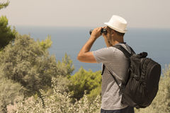 Tourist looking through binoculars on a hill near the sea. Young tourist guy wearing a backpack and looking through binoculars. Sunny summer day at the seaside Royalty Free Stock Photos