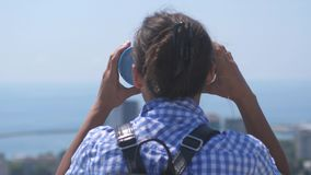 Tourist looking through binoculars at Sochi. Young woman with backpack looking through binoculars from a tower high. Above city on sunny day stock footage