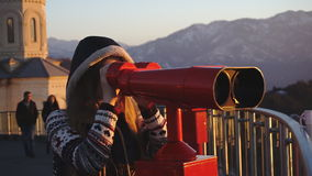 Tourist looking at city through coin-operated binoculars at sunset, medium shot. Travel: young woman tourist looking at city through coin-operated binoculars at stock video footage