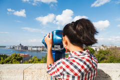 Tourist looking at cityscape. Woman seeing the city over a river through binocular Stock Photography