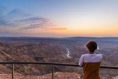 Tourist looking at the Fish River Canyon, scenic travel destination in Southern Namibia. Ultra wide angle view from above, colorfu Stock Photography
