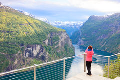 Tourist looking at Geirangerfjord from Flydasjuvet viewpoint Norway Stock Photos