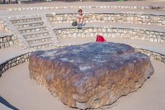 Tourist looking at Hoba meteorite, Namibia, Africa. The meteorite is composed by high density heavy metals, mostly iron and nickel. With traces of cobalt royalty free stock images