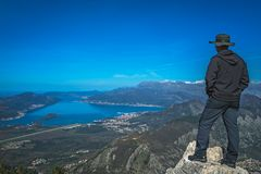 Tourist looking at the Kotor bay. Tourist with a hat standing on a large boulder and admiring the stunning landscape of the Bay of Kotor in Montenegro as seen royalty free stock photography
