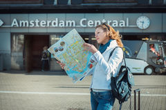 Tourist looking at the map in Amsterdam. Female tourist looking at the map at the central Amsterdam railway station Stock Images