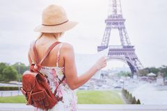 Tourist looking at the map of city Paris near Eiffel tower. Tourism in France Stock Photo
