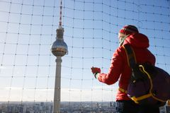 Tourist looking at TV Tower, Fernsehturm, Berlin. Tourist looking at the monumental TV Tower, Fernsehturm, dominating Berlin sky, Germany, from observation deck stock photos