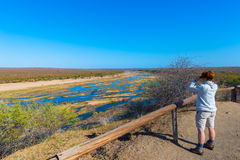 Tourist looking at panorama with binocular from viewpoint over the Olifants river, scenic and colorful landscape with wildlife in
