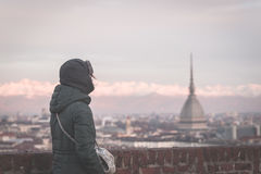 Tourist looking at panoramic view of Torino Turin, Italy from balcony above. Winter time, snowcapped Alps in the background. Sel Royalty Free Stock Photo