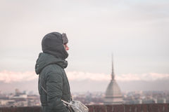 Tourist looking at panoramic view of Torino Turin, Italy from balcony above. Winter time, snowcapped Alps in the background. Sel Royalty Free Stock Photos
