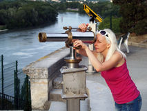 Tourist looking through telescope. Young woman looking through telescope in Avignon, France Stock Images