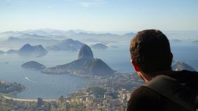 Tourist looking to the Rio harbor and Sugar Loaf Mountain from Corcovado in Rio de Janeiro, Brazil. royalty free stock images