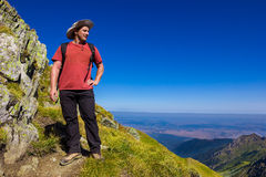 Tourist looking at view during a hiking trip. In mountains Stock Images
