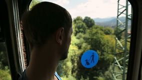 Tourist looking through window when riding cable car, public transportation. Stock footage stock video
