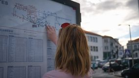 Tourist looks at the bus schedule on the street. Lovely girl looks when her bus arrives stock video