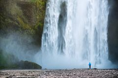 Tourist near Skogafoss waterfall in Iceland. Tourist looks at a huge waterfall Skogafoss. Tourist attraction of Iceland royalty free stock image