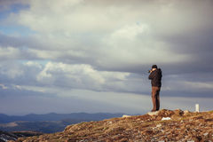 Tourist looks at the landscape. Photographer on top of mountain Royalty Free Stock Photos