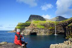A tourist looks at a Mulafossur waterfall in Gasadalur, Faroe Islands