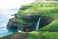 Tourist looks at the Mulafossur waterfall near Gasadalur on Faroe Islands