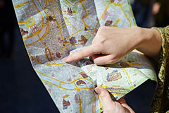 Tourist looks for a route on map Royalty Free Stock Photos