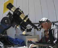 A Tourist Looks Through a Telescope at the Sun Royalty Free Stock Image