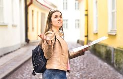 Tourist lost in the city. Confused woman holding map. Tourist lost in the city. Confused woman holding map and spreading hands in old town. Disappointed and Stock Image