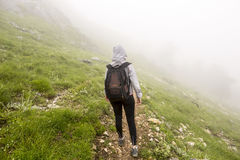 Tourist lost in the fog. High in the mountain. Alone young woman with backpack seen from her back inside dense mist Stock Photos