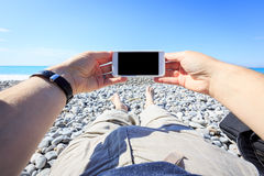 Tourist Lying On The Beach With Phone Stock Photo