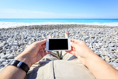 Tourist Lying On The Beach With Phone Royalty Free Stock Photos