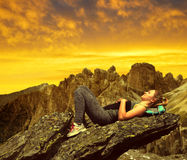 Tourist lying on a rock in Dolomites Royalty Free Stock Image